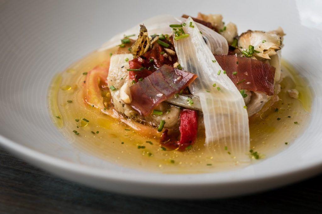 Ensalada de tomate de temporada, escalibada y salazones con dashi y mirin